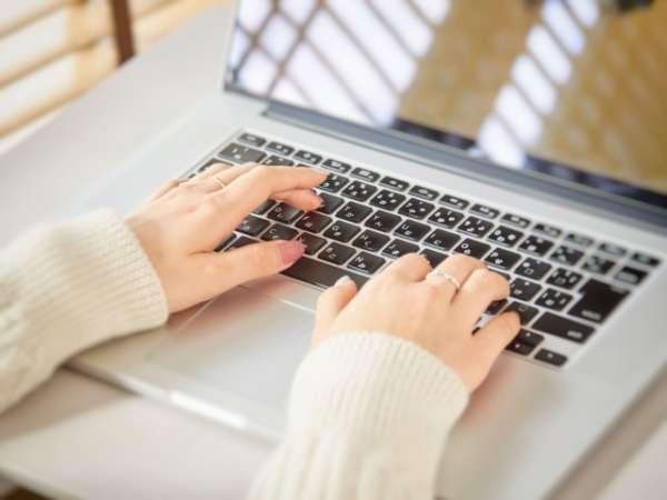 物件を見つけるため、パソコンでウェブ検索している女性の手元