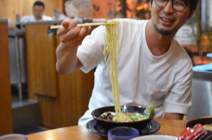 ラーメン店で麺を持ち上げる男性