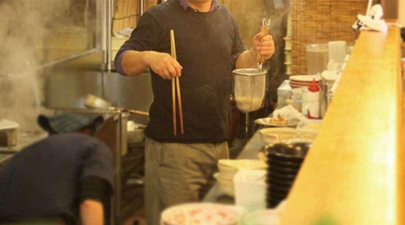 ラーメン店の厨房で麺の湯切りをしている